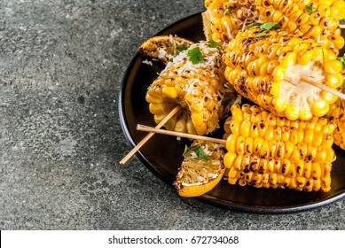 Summer food. Ideas for barbecue and grill parties. Grilled corn grilled on fire. With a sprinkle of cheese (mexican elotes), hot chili pepper, lemon. On a dark stone table, black plate Copy space