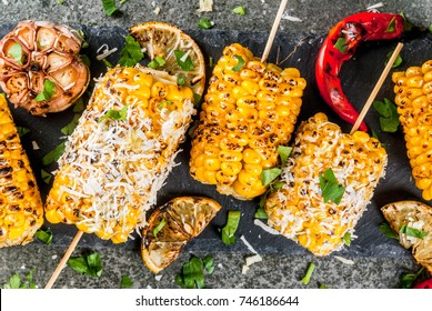 Summer food. Ideas for barbecue and grill parties. Grilled corn grilled on fire. With a sprinkle of cheese (mexican elotes), hot chili pepper and lemon. On a dark stone table. Top close view