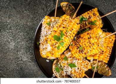 Summer food. Ideas for barbecue and grill parties. Grilled corn grilled on fire. With a sprinkle of cheese (elotes), hot chili pepper, lemon. On a dark stone table, black plate Copy space top view