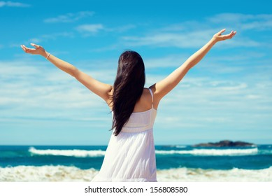 Summer freedom on the beach. Joyful woman raising arms to the sky, enjoying travel and vacation on coast. Playa de Verdicio, Asturias, Spain.