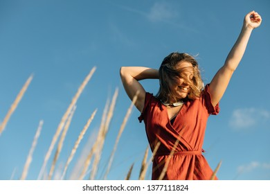 Summer freedom and relaxing leisure. Young happy woman raising arms to feel the breeze at the beach.