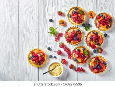 summer french desserts - tarts with lemon custard cream filling topped with raspberries, apricots, blueberry, strawberry, red currants and fresh mint on a wooden table, empty space, flatlay
