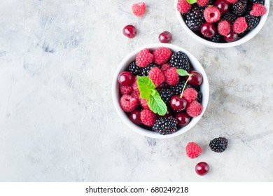 Summer fresh berries in white bowl on gray concrete table background. Top view with copy space. Vegetarian food - raspberry, blackberry and cherry