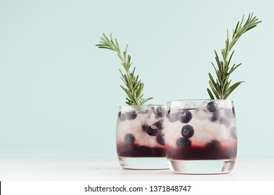 Summer fresh blueberry cocktails in glasses with berry, ice cubes, rosemary on white wood table and pastel mint color wall, copy space.