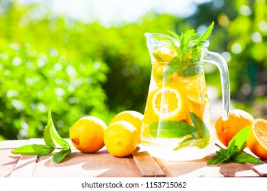 Summer fresh cold drink beverages. Ice Lemonade in the jug and lemons and orange with mint on the table outdoor. Copy space