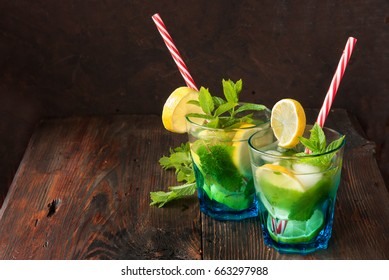 Summer fresh drink. Lemonade with mint in glass on wooden rustic background. Home made Mojito beverage