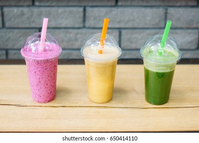 Summer fresh drink. Three colorful nature smoothies. Favorite vegeterian food. Photo of smoothies on a wooden board.