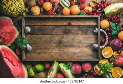 Summer fresh fruit variety with rustic wooden tray in center, top view, copy space, horizontal composition