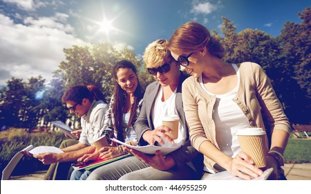 summer, friendship, education and teenage concept - group of happy students with notebooks learning and drinking coffee at campus