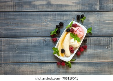 Summer fruit berry breakfast. Healthy banana split breakfast with white and pink ice cream , raspberries, blackberries, mint. On white plate. Top view, copy space