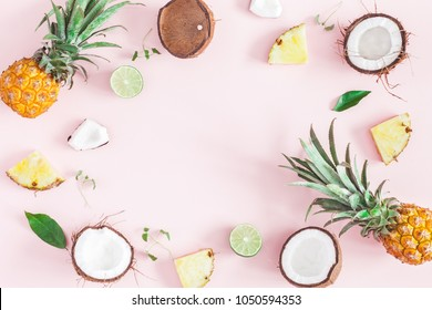Summer fruit composition. Pineapples, coconuts on pastel pink background. Fruit background. Summer concept. Flat lay, top view, copy space
