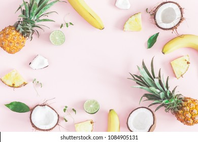 Summer fruit composition. Pineapples, coconuts, bananas on pastel pink background. Fruit background. Summer concept. Flat lay, top view, copy space