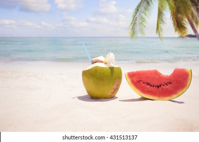 Summer fruit concept with coconut cocktail, watermelon on sandy tropical beach