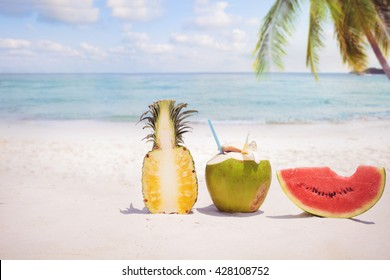 Summer fruit concept with coconut cocktial, watermelon and pineapple on sandy tropical beach