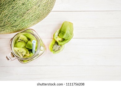 summer fruit concept. melon half kiwi slices in a masonjar on white wooden background flat lay top view