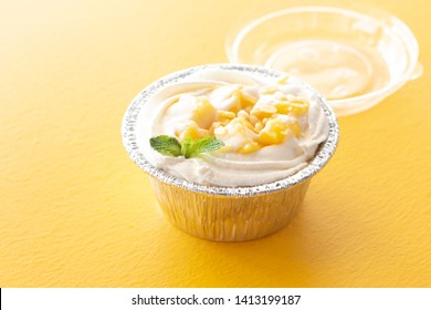 Summer fruit dessert is Mango cheesecake on yellow table background.