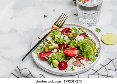 Summer fruit strawberry salad with chicken meat avocado, feta cheese, lettuce and nuts balsamic vinegar, concepts health food.