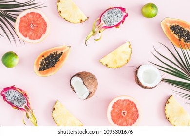 Summer fruits. Tropical palm leaves, pineapple, coconut, papaya, dragon fruit, orange on pastel pink background. Flat lay, top view