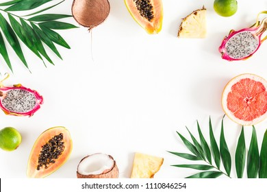 Summer fruits. Tropical palm leaves, pineapple, coconut, papaya, dragon fruit, orange on white background. Flat lay, top view, copy space