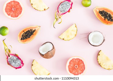 Summer fruits. Tropical pineapple, coconut, papaya, dragon fruit, orange on pastel pink background. Flat lay, top view