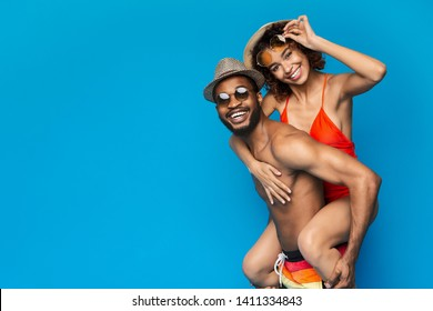 Summer fun. African american couple fooling, man piggybacking his girlfriend, blue studio background, empty space