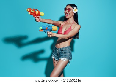 Summer fun. Attractive young Asian woman smiling and shooting with water guns while standing against blue background