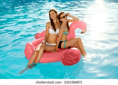 Summer Fun. Fashion Girls On Flamingo In Pool. Beautiful Sexy Women With Fit Bodies In Fashionable Bikini Having Fun, Relaxing On Inflatable Mattress In Swimming Pool. Summer Style. High Resolution.