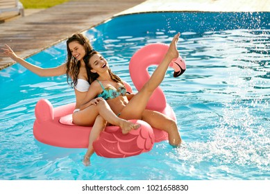 Summer Fun. Fashion Girls On Flamingo In Pool. Beautiful Sexy Women With Fit Bodies In Fashionable Bikini Having Fun, Relaxing On Inflatable Mattress In Swimming Pool. Summer Style. High Resolution.