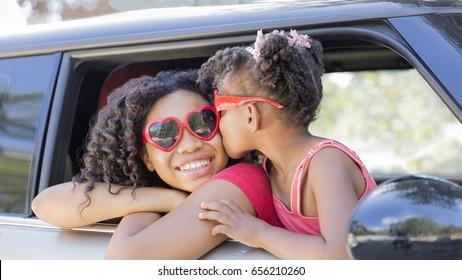 Summer fun! Happy girls or sisters with heart shaped sunglasses in car window. Younger girl kisses older girl on cheek in celebration of love, summer holiday, road trip or Valentines day. Copy space.
