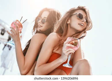 Summer fun has begun. Girls sitting by the pool, drinking cocktails