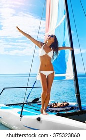Summer Fun. Healthy Happy Woman With Sexy Fit Body In Bikini Enjoying Holidays Travel Vacation Standing On Small Sailing Catamaran At Exotic Beach Resort. Active Lifestyle. Leisure Sporting Activity