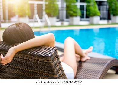 Summer fun in holiday, Happy beautiful woman relaxing sunbathe near luxury swimming pool, summer holiday vacation concept.