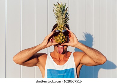 Summer fun. Joyful smiling man showing a tongue, holding a pineapple with sunglasses in front of his face. Outdoors.