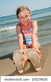 Summer fun - lovely girl playing on sandy beach