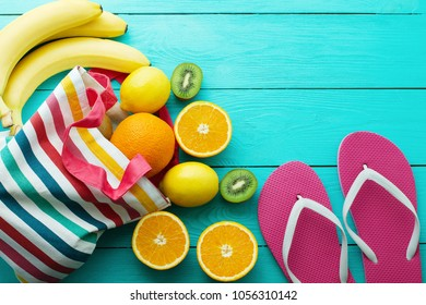 Summer fun time, flip flops and fruits on blue wooden background. Orange, lemon, kiwi, banana fruit , slippers on the floor. Top view and copy space