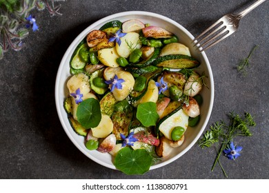 Summer garden vegetable salad with potatoes, roast radishes, broad beans and courgettes