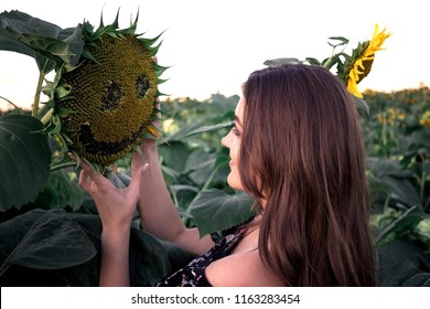 Summer girl. Beautiful cheerful young woman with sunflower enjoying nature and laughing on summer sun flower field. Sunflare, sunbeams, glow sun. Backlight