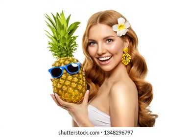 Summer girl Bright woman with a pineapple in her hands with earrings in the form of a tropical leaf, with sun glasses on a white background. Bright summer vacation or sale.