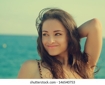 Summer girl looking happy on blue sea and sky background. Closeup vintage portrait