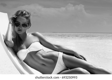 Summer girl model with tanned sexy body. Posing in the white chair on the beach of the tropical island