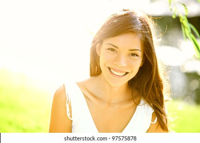 Summer girl portrait. Asian woman smiling happy on sunny summer or spring day outside in park by lake. Pretty mixed race Caucasian / Chinese Asian young woman outdoors.