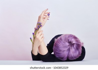 Summer girl with purple hair Beautiful well-groomed hands with wild flowers lying on the table, cosmetics for hands. Care and beauty for skin, moisturizing skin and Spa, contrasting makeup
