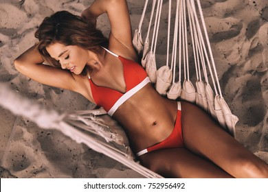 Summer goddess. Top view of attractive young woman in swimwear keeping hands behind and smiling while lying down in hammock outdoors