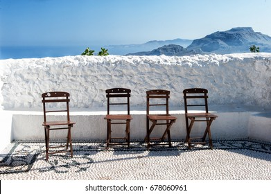 Summer in Greece. Chairs under the white wall. Holidays on the island.