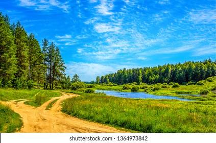 Summer green river road landscape. Summer river road view. River road in summer green forest. Summer green forrest river road landscape