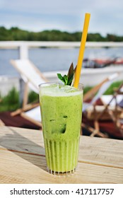 Summer green smoothie cocktail in glass on wooden table.
