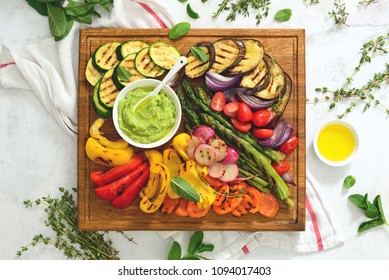 Summer grilled vegetables served with herbs and avocado and feta dip on wooden board, view from above