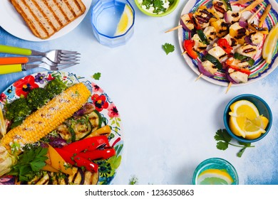 Summer grilling chicken kabobs served with vegetables and water with lemon in glasses, top view