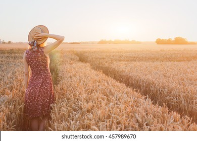summer happy young woman in wheat field by sunset, daydream, beautiful background with place for text