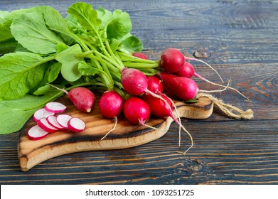 Summer harvested red radish. Growing organic vegetables. Large bunch of raw fresh juicy garden radish on dark boards ready to eat.